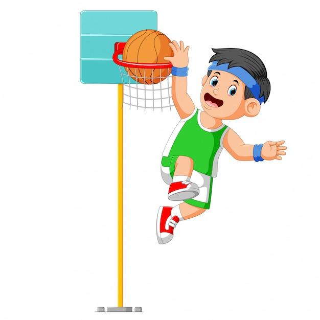 O menino está pulando para fazer o placar na cesta Vetor Premium