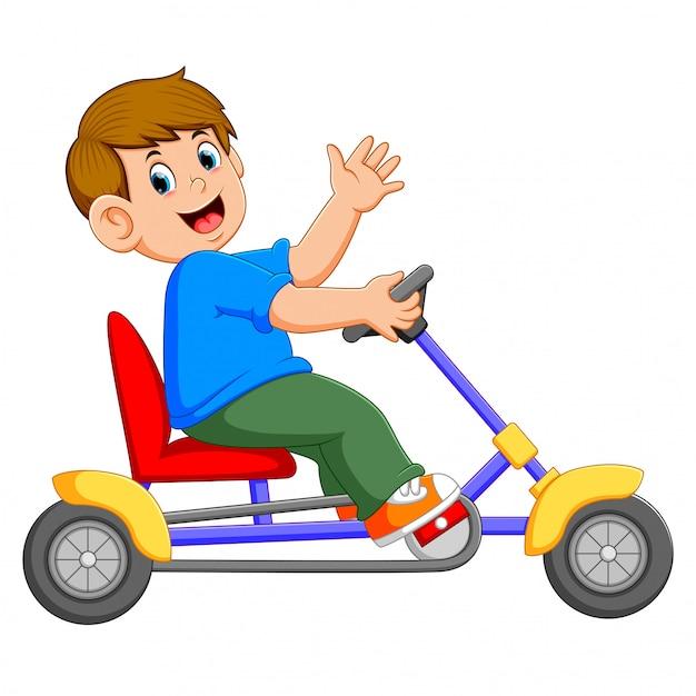 O menino está sentado e andando no triciclo Vetor Premium