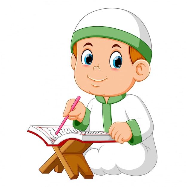 O menino está sentado e lendo al quran Vetor Premium