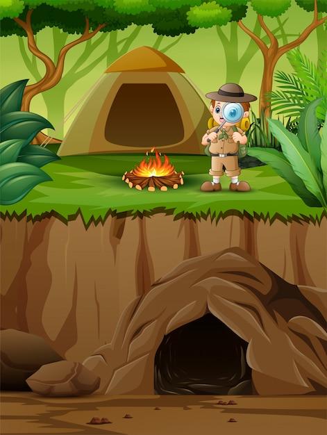 O menino explorador perto de sua tenda Vetor Premium