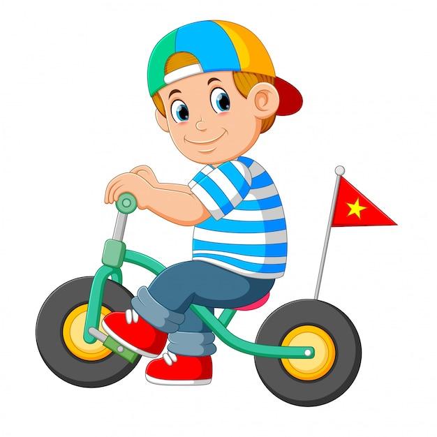 O menino usa o boné está brincando com a pequena bicicleta Vetor Premium