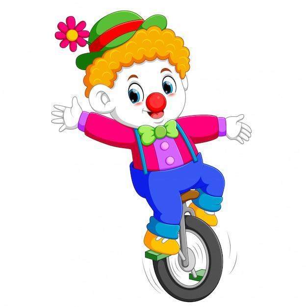 O menino usa o traje de circo e em pé no monociclo Vetor Premium