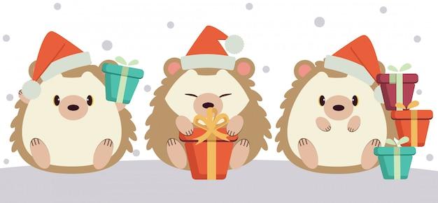 O personagem de ouriço fofo sentado no chão e segurando uma caixa de presente na temporada de inverno. Vetor Premium