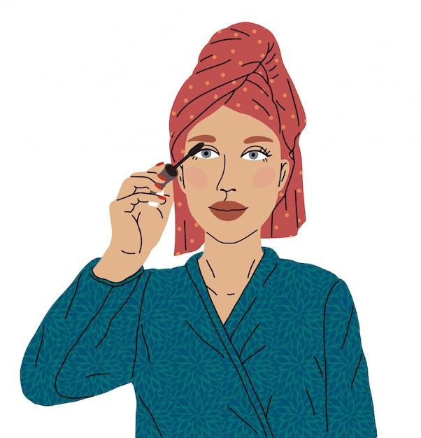 O rímel de tinta para olhos de mulher bonita saiu do chuveiro com uma toalha na cabeça e um roupão macio. conceito de cuidar de seu corpo e imagem. amor por si mesmo, maquiagem, blogueiro de maquiagem. Vetor Premium