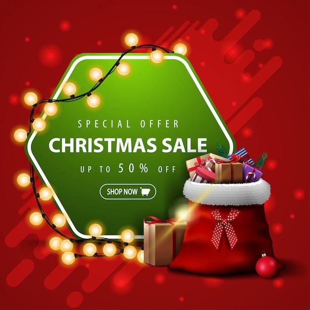 Oferta especial, venda de natal, desconto de até 50%, faixa quadrada vermelha e verde com guirlanda e bolsa de papai noel com presentes Vetor Premium