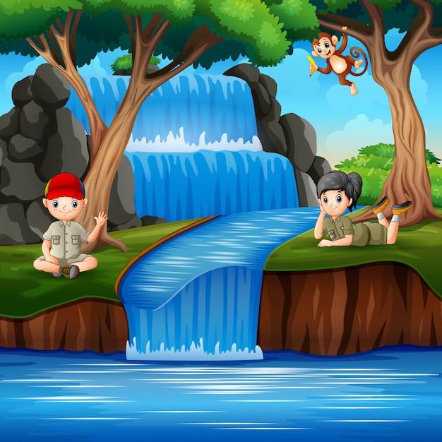 Os escoteiros desfrutando na cachoeira Vetor Premium