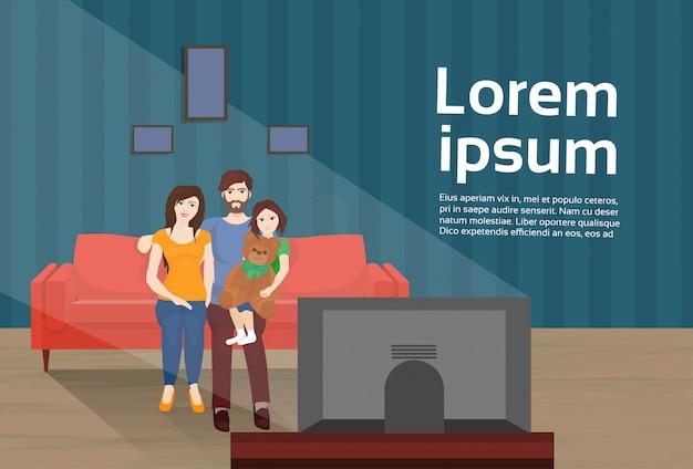 Os pais com filha olham a tevê sentar-se no sofá e comem a pipoca na sala de visitas. modelo de texto Vetor Premium