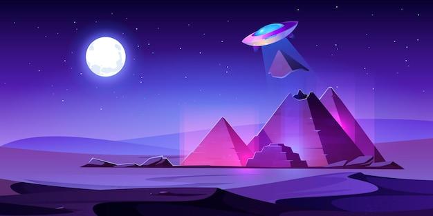 Ovni rouba o topo das pirâmides do egito no deserto noturno, o disco alienígena puxa o pedaço da tumba do faraó egípcio em feixe de luz. Vetor grátis