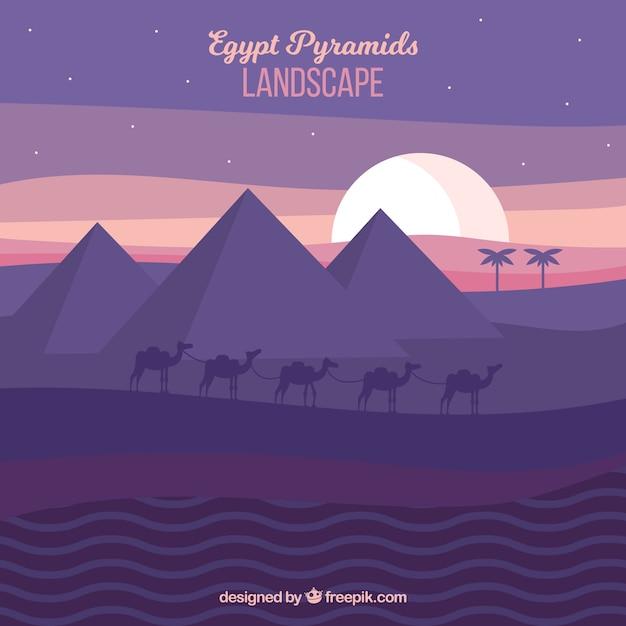 Paisagem de pirâmides do egito com caravana de camelos à noite Vetor grátis