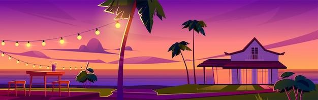 Paisagem tropical de verão com bangalô na praia do oceano, mesa e cadeiras no terraço ao pôr do sol Vetor grátis