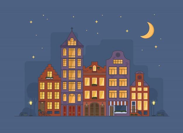 Paisagem urbana aconchegante de amsterdã à noite com lua e estrelas no céu Vetor Premium