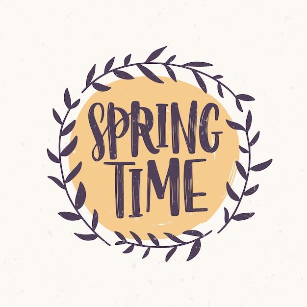 Palavra de primavera escrita com fonte elegante dentro frame redondo ou grinalda feita de galhos e folhas. letras de primavera decoradas com elemento natural isolado no fundo branco. ilustração. Vetor Premium