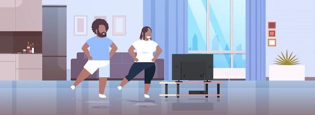Par, exercitar, durante, tv, mostrar, homem africano, mulher, treinamento, enquanto, assistindo, programa aptidão Vetor Premium
