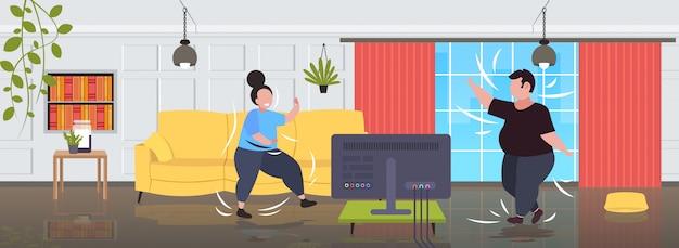Pares obeso gordo exercitar durante programa de tv overweight homem mulher treinamento enquanto assiste programa de fitness home workout conceito de perda de peso moderna sala de estar interior Vetor Premium