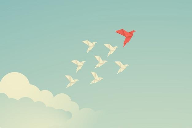 Pássaro de papel vermelho do origami que conduz entre o branco. Vetor Premium