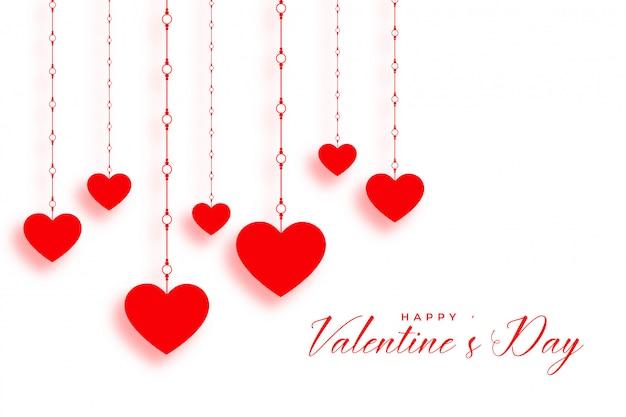 Pendurando corações vermelhos em branco dia dos namorados Vetor grátis