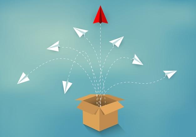 Pense fora da caixa. avião de papel vermelho e branco ejetado da caixa marrom Vetor Premium