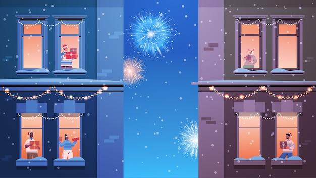 Pessoas em chapéus de papai noel misturam raça vizinhos em pé nas janelas olhando fogos de artifício no céu ano novo natal feriados celebração auto-isolamento conceito construção fachada de casa horizontal vetor doente Vetor Premium