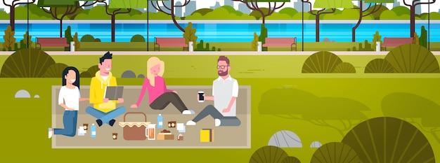 Pessoas felizes fazendo piquenique no parque grupo de jovens homens e mulheres sentadas na grama relaxando e se comunicando horizontal Vetor Premium