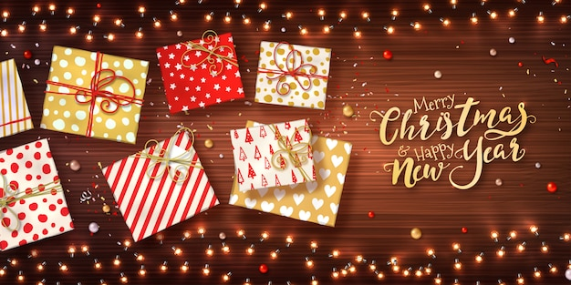 Plano de fundo natal e ano novo com caixas de presente, guirlandas de natal de luzes, enfeites e confetes de brilho na textura de madeira. Vetor Premium