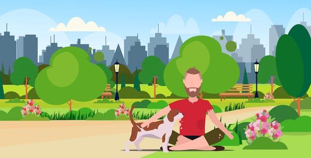 Pobre homem barbudo com cachorro sentado no mendigo do parque urbano, implorando por ajuda sem-teto conceito de desemprego paisagem urbana de fundo de paisagem comprimento total plano horizontal Vetor Premium