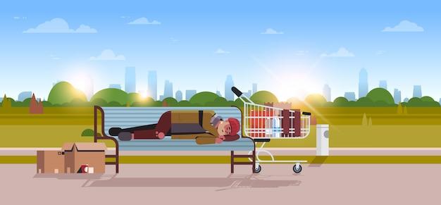 Pobre homem dormindo ao ar livre mendigo bêbado deitado no banco de madeira cidade desabrigada parque paisagem nascer do sol Vetor Premium