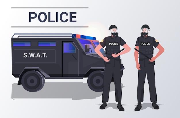 Policiais com equipamento tático casal de policiais de choque em pé perto de manifestantes de carro Vetor Premium