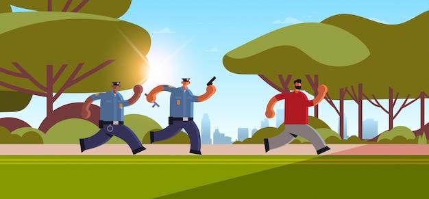 Policiais com pistolas perseguindo criminoso ladrão fugindo de policiais em uniforme autoridade autoridade justiça serviço conceito urbano parque paisagem urbana fundo horizontal comprimento total Vetor Premium