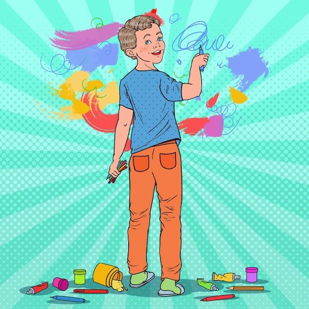 Pop art menino criativo desenho na parede. criança alegre pintura com giz de cera no papel de parede. Vetor Premium