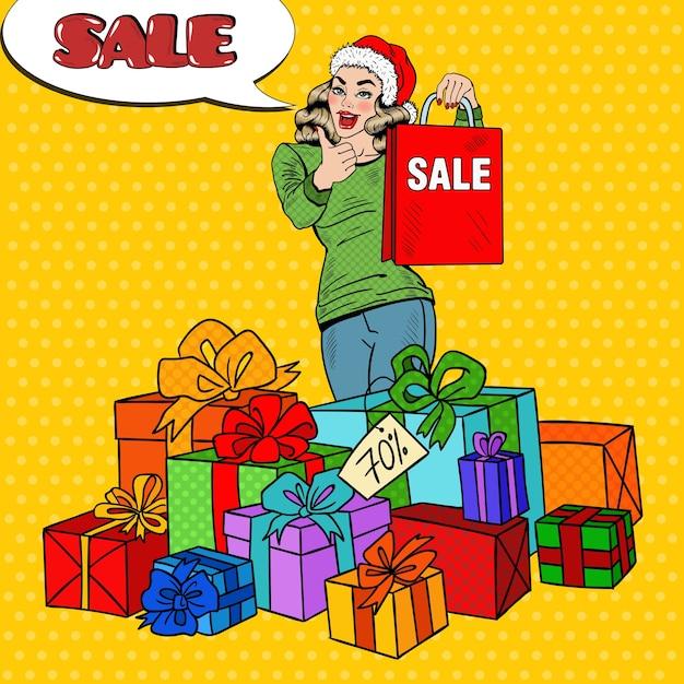 Pop art mulher feliz no chapéu de papai noel com sacola de compras e caixas de presente enorme na venda de natal. Vetor Premium