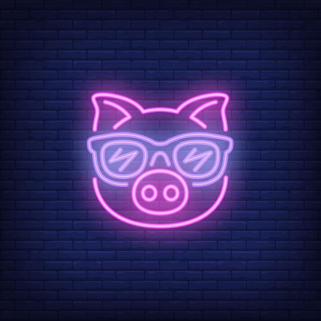 Porco bonito do rosa dos desenhos animados nos óculos de sol. elemento de sinal de néon. anúncio brilhante da noite. Vetor grátis
