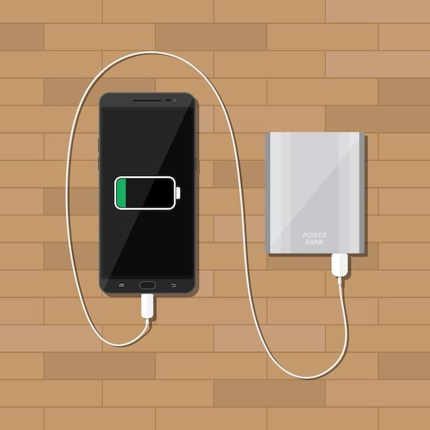Powerbank cobrando smartphone na mesa de madeira Vetor Premium