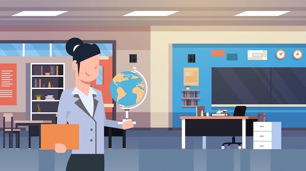 Professor feminino, segurando, globo, sobre, sala aula, interior, escola, sala aula Vetor Premium