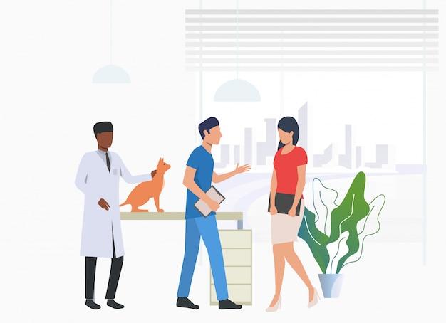 Proprietário do gato visitando e conversando com médicos veterinários Vetor grátis
