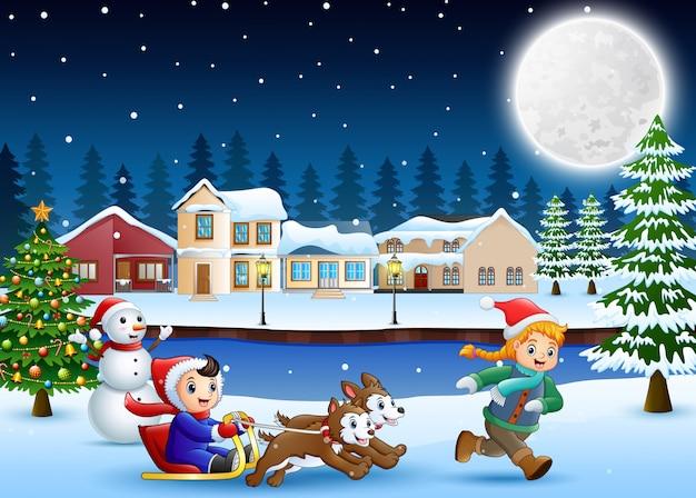 Rapaz dos desenhos animados, montando o trenó na aldeia a nevar com o garoto em execução Vetor Premium