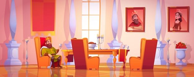 Rei segurando o cálice sentado à mesa com comida Vetor grátis