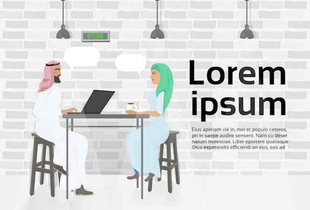 Reunião árabe do homem e da mulher de negócio no centro moderno de coworking que trabalha no laptop. modelo de texto Vetor Premium