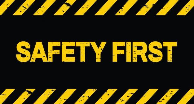 Segurança primeiro. linha preta e amarela listrada. em construção Vetor Premium