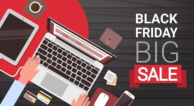 Sexta-feira negra grande venda banner design com mãos de homem, digitando no computador portátil acima vista Vetor Premium