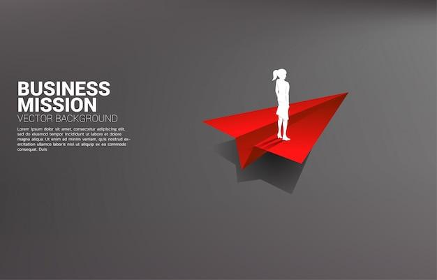 Silhueta da empresária em pé no avião de papel origami vermelho. conceito de negócio de liderança, iniciar negócios e empreendedor Vetor Premium