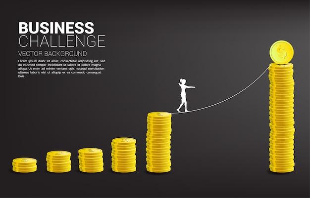 Silhueta da mulher de negócios que anda na maneira da caminhada da corda ao gráfico dourado da pilha da moeda. conceito para o risco e o desafio de negócios. Vetor Premium
