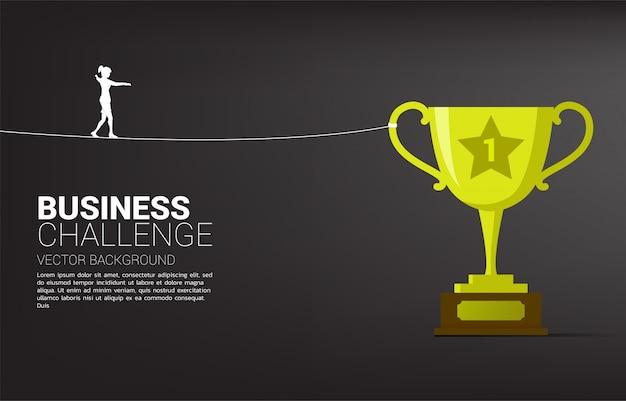 Silhueta da mulher de negócios que anda na maneira da caminhada da corda ao troféu dourado. conceito para o risco e o desafio de negócios. Vetor Premium