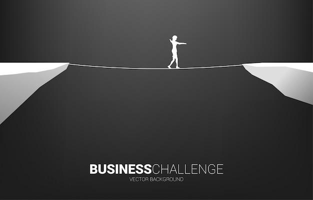Silhueta de empresária andando na maneira de andar de corda. conceito de risco de negócios e desafio no plano de carreira Vetor Premium