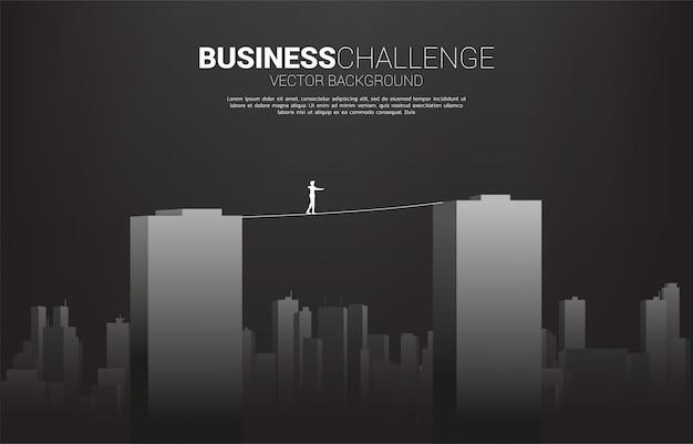 Silhueta, de, homem negócios, andar, ligado, corda, passeio, maneira, através, predios., conceito, para, risco negócio, e, desafio, em, carreira Vetor Premium