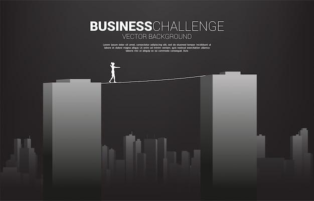 Silhueta de mulher de negócios andando na corda a pé através do edifício. conceito de risco de negócios e desafio na carreira Vetor Premium