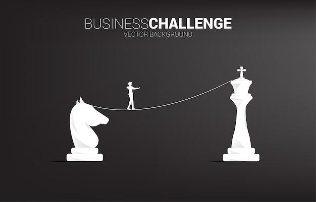 Silhueta do empresário andando na corda andar caminho de cavaleiro ao rei xadrez. Vetor Premium