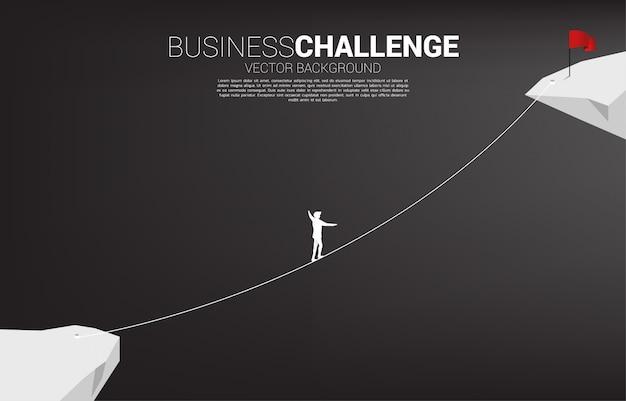Silhueta do empresário andando na corda andar maneira a bandeira vermelha. Vetor Premium