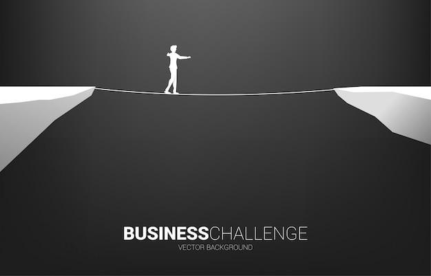 Silhueta do empresário andando na maneira de andar a corda. conceito de risco de negócios e desafio no plano de carreira Vetor Premium