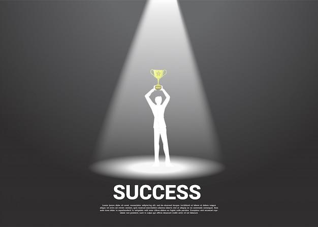 Silhueta do empresário com o troféu de ouro no centro das atenções. Vetor Premium
