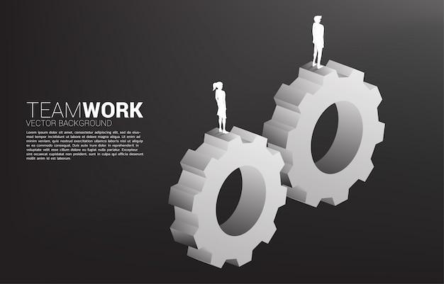 Silhueta do empresário e empresária permanente nas engrenagens para trabalhar juntos. conceito de trabalho em equipe de negócios. Vetor Premium